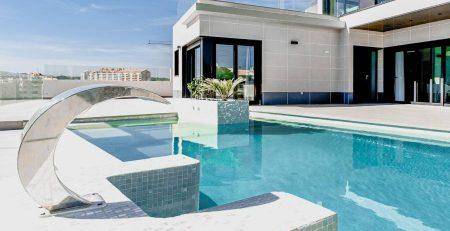 Une fontaine pour piscine au bord d'une piscine de villa contemporaine